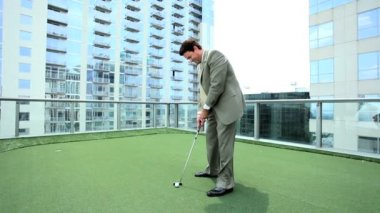 Young Businessman Practicing Golf on Office Rooftop — Stock Video