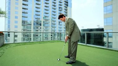 Young Businessman Practicing Golf on City Office Roof — Stock Video