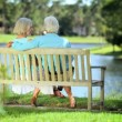 Older Couple on Park Bench Enjoying the View - Stock Photo