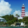 Tropical Island Lighthouse with Passing Yachts - Stock Photo