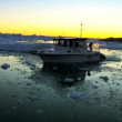 Stock Video: Nautical vessel at sunset in ice floes with icebergs