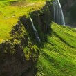 Stock Video: Aerial view of Glacial Meltwater Forming Waterfall, Iceland