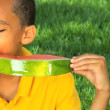 Young Ethnic Boy Enjoying Healthy Water Melon - Stock Photo