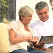 Middle Aged Couple Using Wireless Tablet — Stock Video