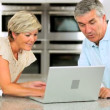 Wireless Laptop Used by Mature Couple in Kitchen — Stock Video