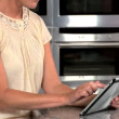 Mature Female Using Wireless Tablet in Kitchen - Стоковая фотография