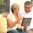 Middle Aged Couple Using Online Webchat at Home - Стоковая фотография