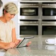 Caucasian Couple in Home Kitchen Using Wireless Tablet - Стоковая фотография