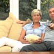 Mature Caucasian Couple Enjoying TV & Popcorn — Stock Video #23259910