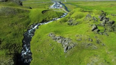 Aerial view of a plateau in the Arctic region with meltwater forming a cascading waterfall from the ridge, Iceland