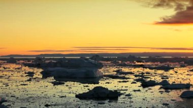 Golden sunset over melting ice floes and icebergs an affect of global warming arctic region