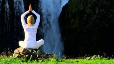 Fêmea em branco realizando yoga pela cachoeira — Vídeo stock