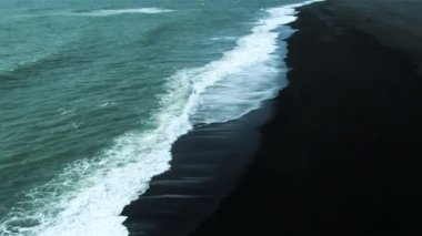 Aerial view featuring an arctic coastline with waves crashing onto a black volcanic ash beach, Iceland