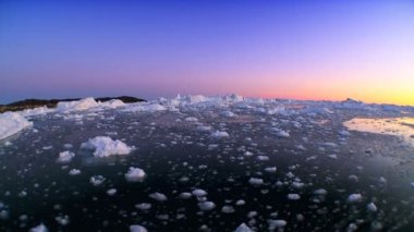 Floating arctic ice floes seen at sunset in wide angle