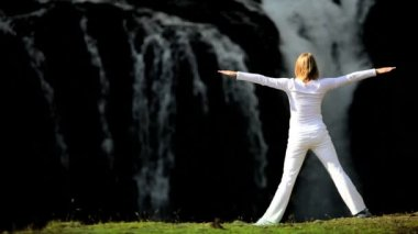 Female in White Performing Yoga by Waterfall — Stock Video