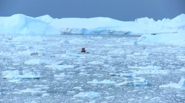 Nautical vessel between ice floes and icebergs an affect of global warming arctic region