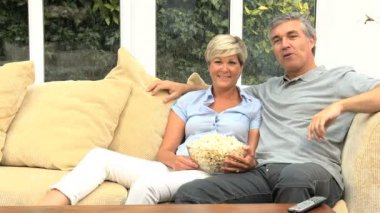 Mature Couple Eating Popcorn in Front of TV — Stock Video