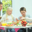 Young Family Eating Healthy Meal - Stock Photo