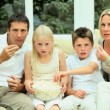 Young Family Watching Movie Together with Popcorn - Stock Photo
