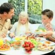 Young Family Enjoying a Healthy Meal - Stock Photo