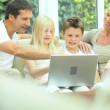 Young Caucasian Family Using Laptop on Sofa — Stock Video
