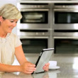 Smart Mature Female Using Wireless Tablet in Kitchen — Stock Video