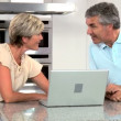 Mature Couple Using Wireless Latop in Home Kitchen - Foto de Stock