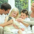 Young Caucasian Family with Pet Dog - Stock Photo