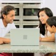 Young Asian Family Using Laptop in Kitchen - Stock Photo