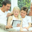 Caucasian Family Playing on Wireless Tablet - Stock Photo