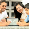 Asian Family Playing on Wireless Tablet - Stock Photo