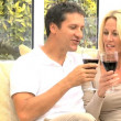 Caucasian Couple at Home Drinking Red Wine - Stock Photo