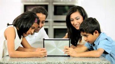 Jeune famille ethnique avec une tablette sans fil en cuisine — Vidéo