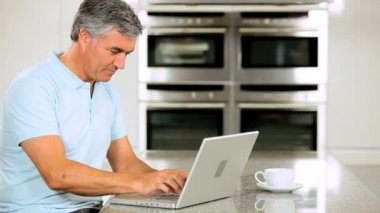 Mature Male Using Laptop Pleased with Online Results — Stock Video