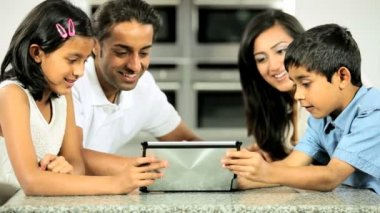 Ethnic family using a wireless tablet on the worktop in their kitchen