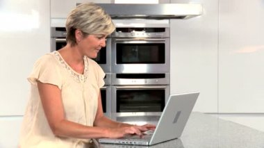 Middle Aged Lady with Laptop in Kitchen — Stock Video