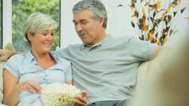 Attractive Mature Couple Watching TV with Popcorn — Stock Video