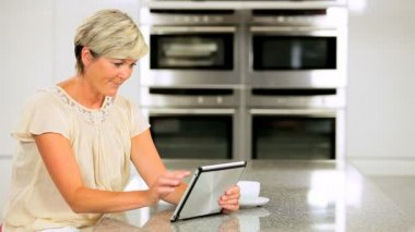 Attractive Mature Female Using Wireless Tablet in Kitchen — Stock Video