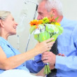 Senior Husband Bringing Wife Flowers in Hospital - Stock Photo