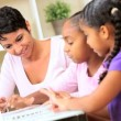 Royalty-Free Stock Vektorový obrázek: Cute Little African American Girls Playing on Laptop