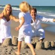 Young Children Running to Parents on Beach — Vídeo Stock