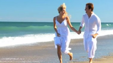 Young Caucasian Couple Running on the Beach — Stock Video