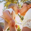 Royalty-Free Stock Vector Image: Young Mom Kissing Baby Son Outdoors