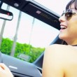 Young Girls Driving in Open Top Car - Stock Photo