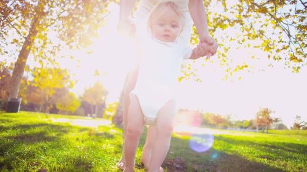 Bebé feliz apoyada por su madre como ella practica caminando — Vídeo de stock