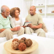 Stock Video: Ethnic Son and Senior Parents Using Wireless Tablet