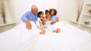 Ethnic Sisters and Grandparents Wireless Tablet Bed — Stock Video