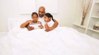 Tableta inalámbrica cama familia afroamericana — Vídeo de Stock