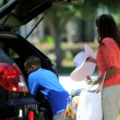 Boy helping parents pack car — Stock Video #49375145