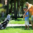 Father teaching son playing golf — Stock Video #49378395